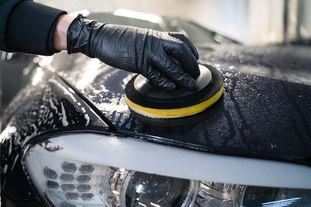 El hombre limpia el capó del coche con una esponja circular.