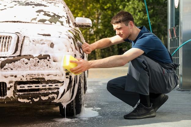 El hombre limpia el coche con una esponja.