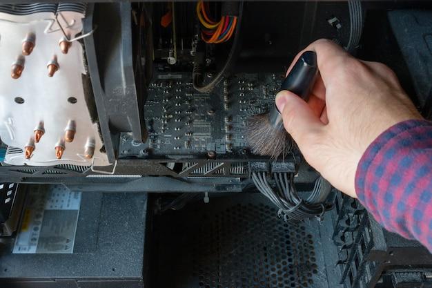 El hombre limpia una computadora del primer plano de polvo