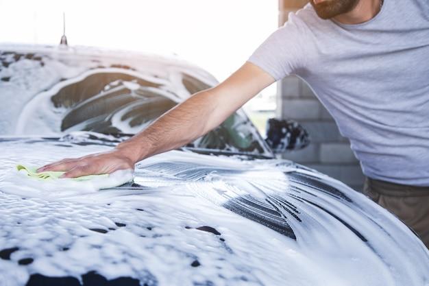 Un hombre limpia la espuma del coche con un trapo. lavado de autos