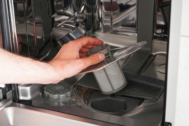 Un hombre limpia el filtro en el lavavajillas.