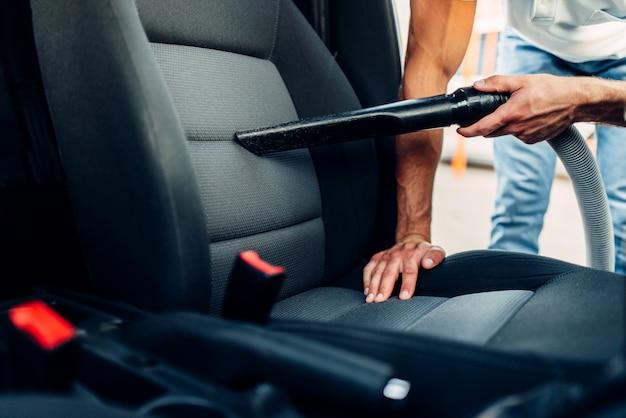 El hombre limpia el interior del coche con aspiradora