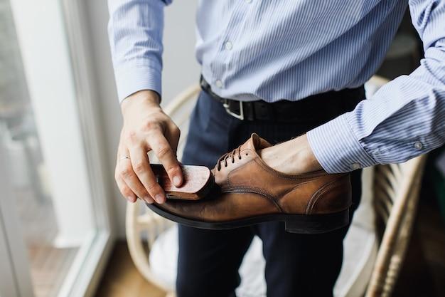El hombre limpia los zapatos con un cepillo de suciedad