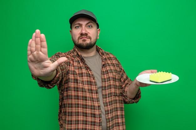 Hombre limpiador eslavo confiado que sostiene la esponja en el plato y gesticula la señal de stop
