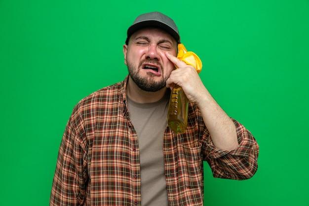 Hombre limpiador eslavo llorando sosteniendo paños de limpieza y limpiador en aerosol
