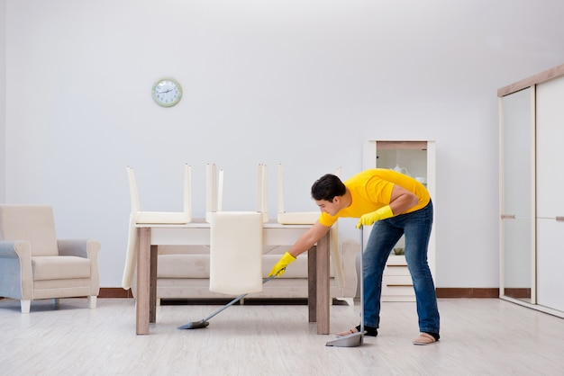Hombre limpiando la casa ayudando a su esposa