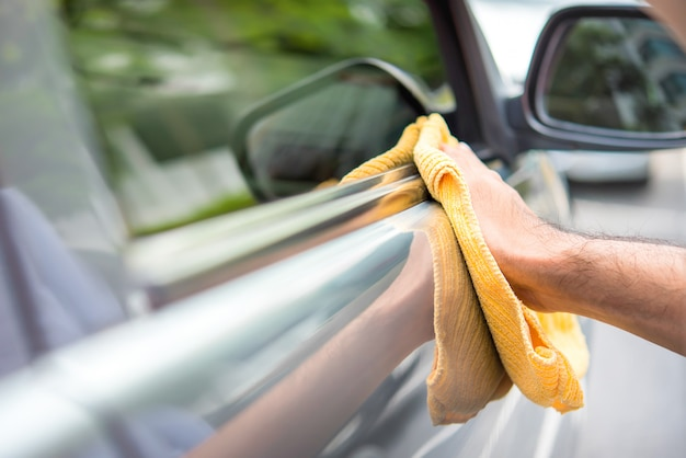 Un hombre limpiando un coche con un paño de microfibra amarillo