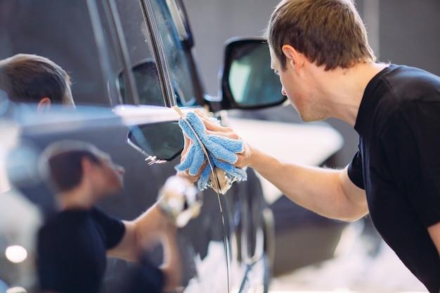 El hombre está limpiando con un cuerpo de tela de un auto brillante.