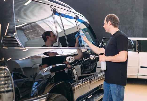 El hombre está limpiando con un cuerpo de tela de un coche brillante.