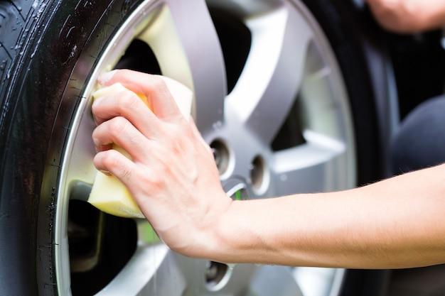Hombre limpiando la llanta de la rueda mientras se lava el auto
