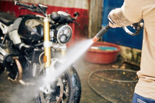 Hombre limpiando motos en el lavado de coches, enfoque selectivo