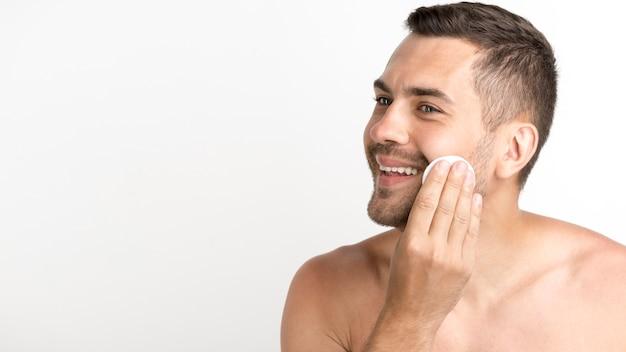 Hombre limpiando la piel de la cara con almohadillas de algodón de bateo sobre fondo blanco.