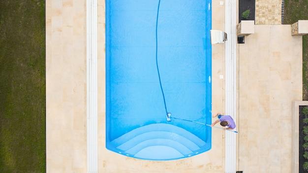 Hombre limpiando la piscina con un aspirador de tubos temprano