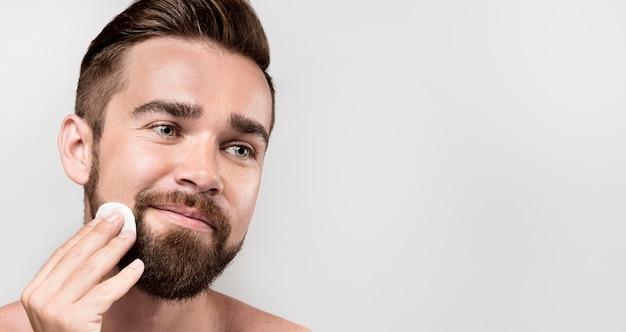 Hombre limpiando su rostro con un disco de limpieza con espacio de copia