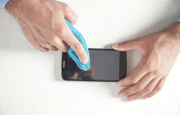 Hombre limpiando su teléfono inteligente en la oficina.