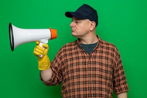 Hombre de limpieza en camisa a cuadros y gorra con guantes de goma sosteniendo megáfono mirando a un lado con expresión de confianza de pie sobre fondo verde