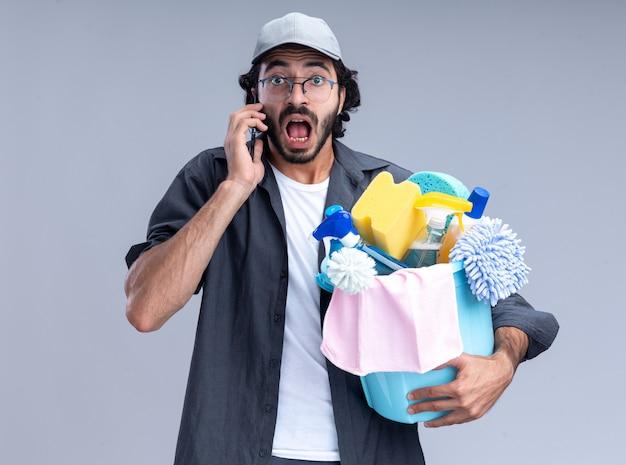 Hombre de limpieza guapo joven asustado con camiseta y gorra sosteniendo un cubo de herramientas de limpieza y habla por teléfono aislado en la pared blanca