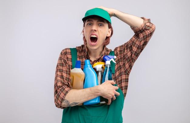 Hombre de limpieza joven emocional en mono de camisa a cuadros y gorra sosteniendo suministros de limpieza mirando gritando de pánico