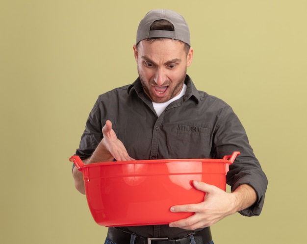 Hombre de limpieza joven con ropa casual y gorra sosteniendo la cuenca mirándolo confundido de pie sobre la pared verde