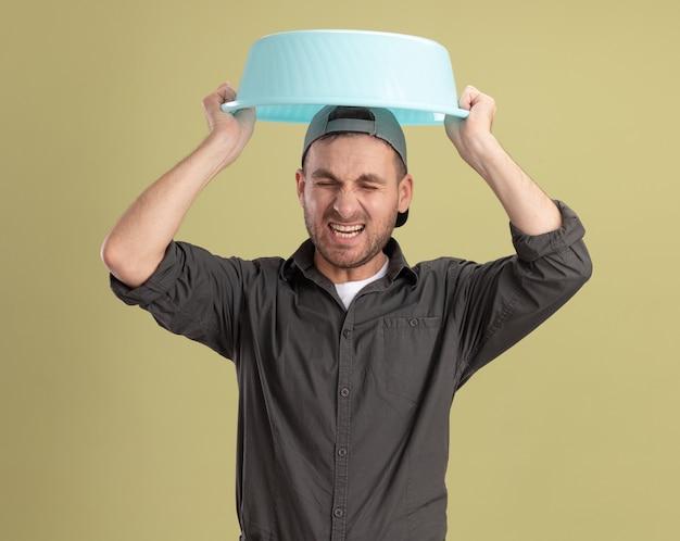 Hombre de limpieza joven con ropa casual y gorra sosteniendo la cuenca sobre su cabeza con expresión molesta gritando de pie sobre la pared verde
