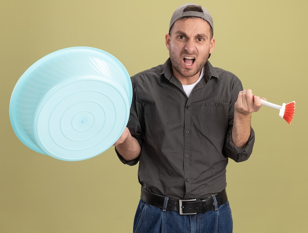 Hombre de limpieza joven con ropa casual y gorra sosteniendo lavabo y cepillo de limpieza gritando con expresión molesta de pie sobre la pared verde