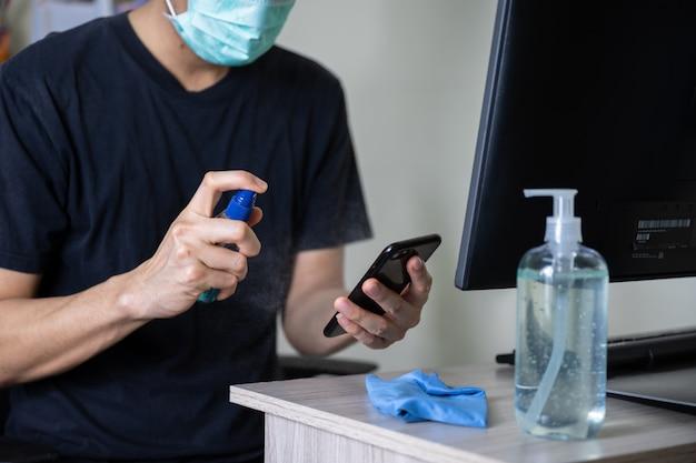 Hombre limpio teléfono móvil con alcohol en aerosol
