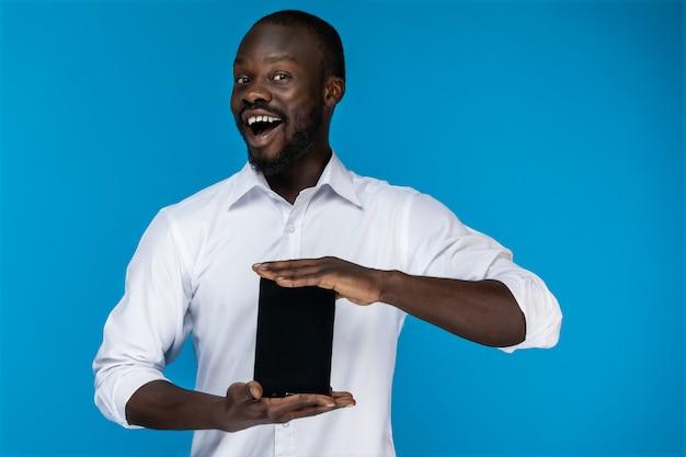 Hombre lindo sonríe y sostiene una tableta