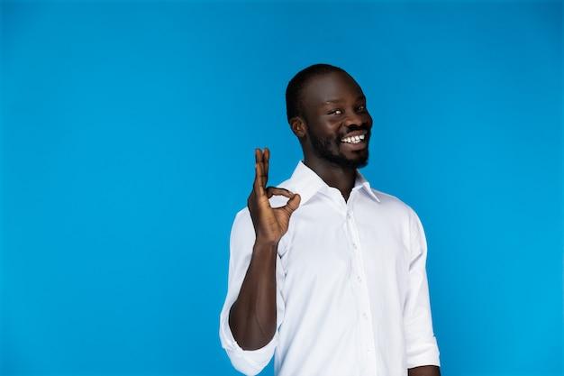 Hombre lindo sonriente muestra bien con sus dedos