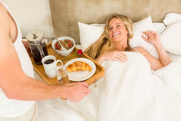 Hombre lindo trayendo el desayuno a su novia en la cama