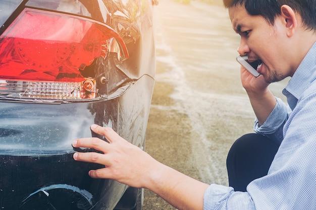 El hombre está llamando a la compañía de seguros por reclamar su accidente automovilístico dañado en accidente de tráfico