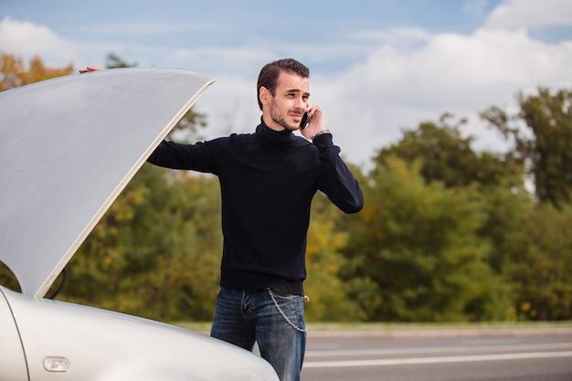 Hombre llamando por teléfono para obtener ayuda con su auto dañado