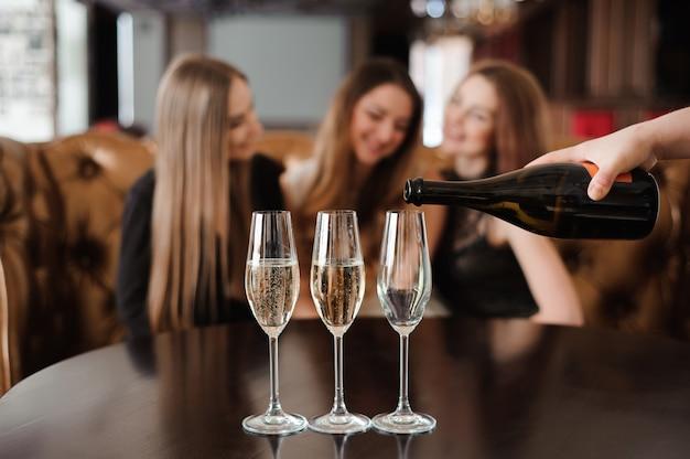 El hombre llena copas de champán para tres hermosas mujeres jóvenes en el restaurante