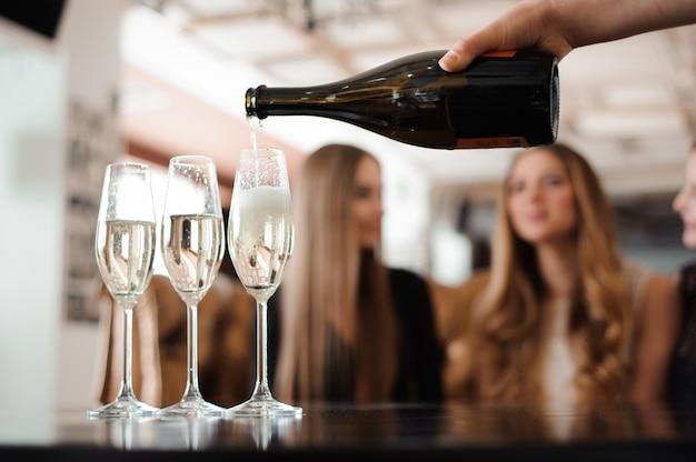 Hombre llena copas de champán para tres hermosas mujeres jóvenes