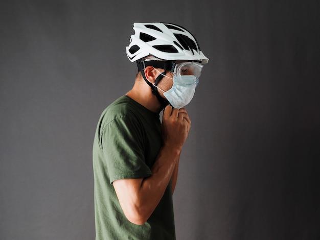 El hombre lleva una camiseta verde, mascarilla y gafas protectoras, sujetadores de casco de bicicleta.