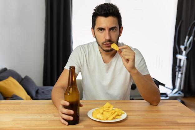Un hombre lleva un estilo de vida equivocado, come papas fritas y bebe cerveza.