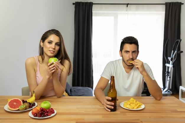 Un hombre lleva un estilo de vida equivocado, come papas fritas y cerveza.
