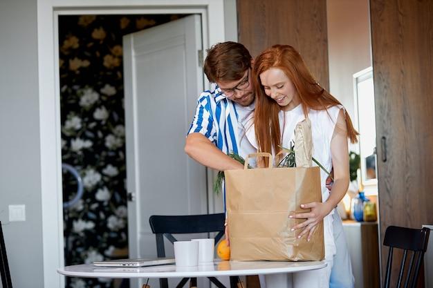 El hombre lleva el paquete con productos mientras la mujer trabaja en casa