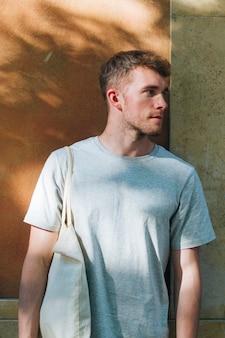 Hombre llevando bolsa de tela y de pie cerca de la pared mirando a otro lado