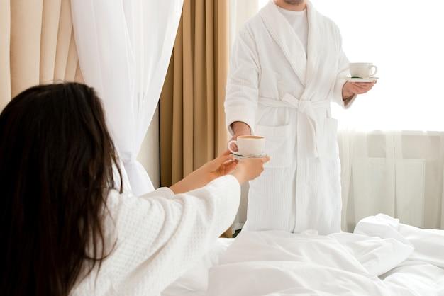 Hombre llevando café a su novia acostada en la cama