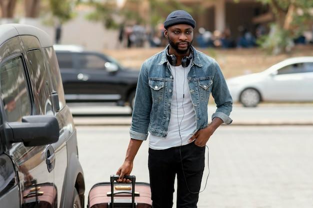 Hombre llevando equipaje de tiro medio