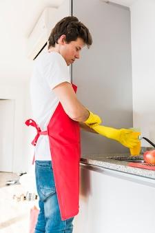 Hombre, llevando, guante amarillo, en, cocina