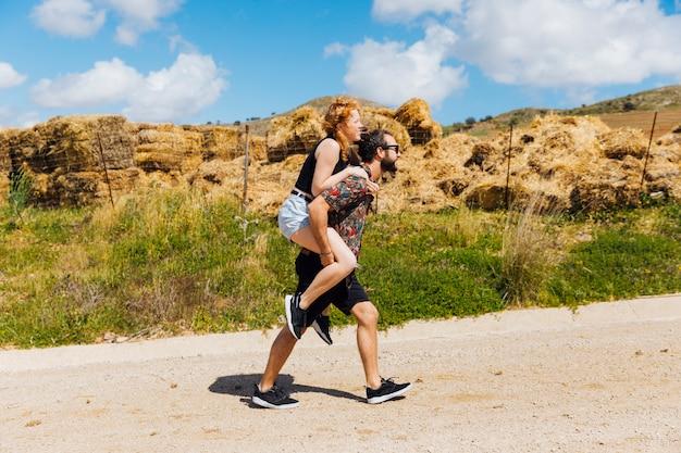 Hombre llevando a mujer en la espalda