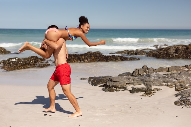Hombre llevando a mujer sobre los hombros en la playa bajo el sol