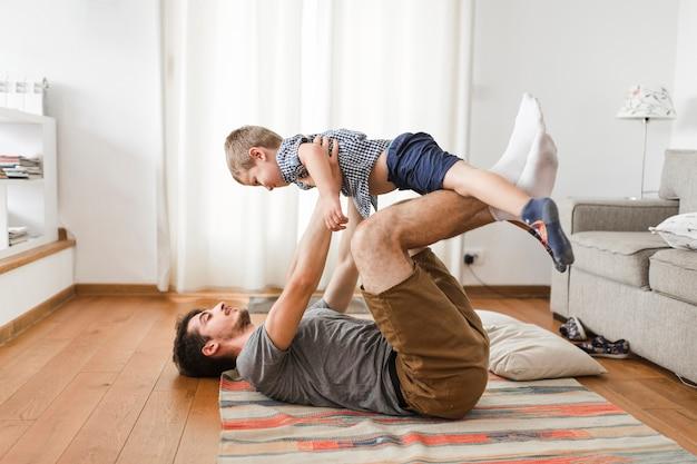 Hombre llevando a su hijo en la pierna mientras hace ejercicio.