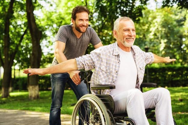 Hombre llevar padre en silla de ruedas. riendo hombres.