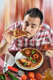 Hombre loco hambriento comiendo pizza en un restaurante