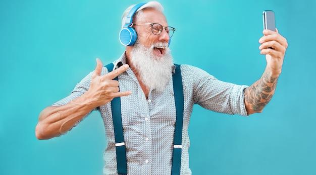 Hombre loco mayor que usa la aplicación de teléfono inteligente para crear una lista de reproducción con música rock - tipo de tatuaje moderno que se divierte con la tecnología del teléfono móvil - tecnología y concepto alegre de estilo de vida para personas mayores - centrarse en la cara