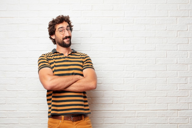 Hombre loco o tonto joven que gesticula y que expresa emociones contra fondo de la pared de ladrillo