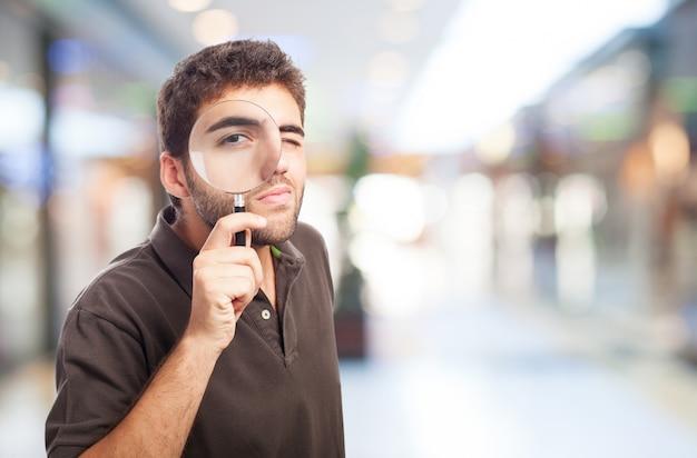 Hombre con una lupa en un centro comercial