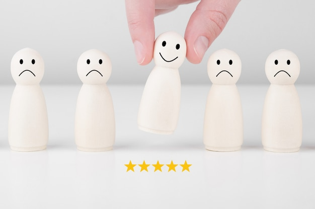 El hombre de madera le da una calificación de 5 estrellas y una cara sonriente. concepto de servicio al cliente y encuesta de satisfacción.